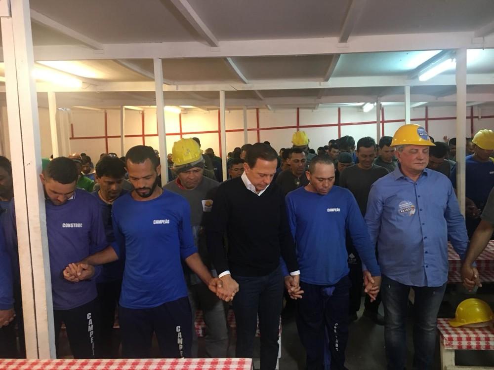 Doria dá a mão aos operários durante oração em obra no Centro de SP — Foto: Giba Bergamim/TV Globo